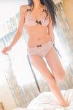 Sexig ung kvinna i damunderkläderbanhoppning på sängen Arkivfoto