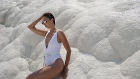 Sexig ung kvinna i det vita baddräktanseendet på ett vitt berg stock video