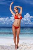 Sexig ung kvinna i en röd bikini på stranden royaltyfri fotografi