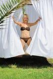 Sexig ung kvinna som kopplar av i himmelssäng Royaltyfri Foto