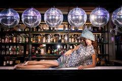 Sexig ung kvinna som ligger på stången på en nattdiskoklubba Arkivbild