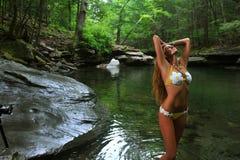 Sexig ung kvinna som poserar i märkes- bikini på exotiskt läge av bergfloden Arkivfoto