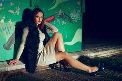 Sexig ung kvinna som poserar på väggen med grafitti på natten Royaltyfri Fotografi