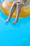 Sexig ung kvinna som tätt svävar i en rubber cirkel, ben upp Royaltyfri Fotografi
