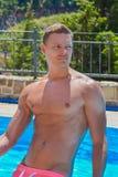Sexig ung man i ljust blått koppla av för simbassäng Royaltyfria Bilder