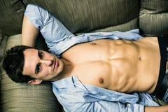 Sexig ung man på soffan fotografering för bildbyråer