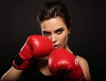 Sexig ursnygg kvinna med mörkt hår i sporthandskar för att boxas arkivfoton