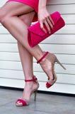 Sexig woman& x27; s lägger benen på ryggen med trendiga rosa höga häl och handväskan Royaltyfria Foton