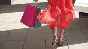 Sexiga ben av en härlig flicka som går med shoppingpåsar långsam rörelse arkivfilmer