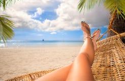 Sexiga ben av en kvinna som ligger i en hängmatta Arkivfoton