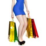 Sexiga ben för kroppsdel, flicka med färgrika shoppingpåsar i blåttse Royaltyfri Foto