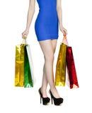 Sexiga ben för kroppsdel, flicka med färgrika shoppingpåsar i blåttse Arkivbild
