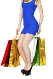 Sexiga ben för kroppsdel, flicka med färgrika shoppingpåsar i blåttse Royaltyfri Bild