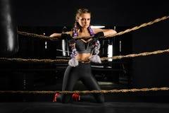 Sexiga den lutade boxningflickan knäfaller på rep av konkurrenscirkeln Trendig stående arkivbilder