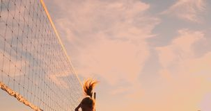 Sexiga flickavolleybollspelare passerar bollen nära det netto och slår bollen på solnedgången i ultrarapid lager videofilmer