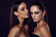Sexiga flickor med makeup för mörkt hår och aftonmed smycket Arkivfoton