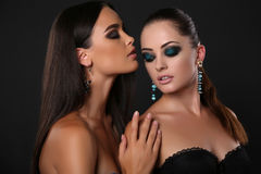 Sexiga flickor med makeup för mörkt hår och aftonmed smycket Royaltyfri Foto