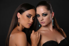 Sexiga flickor med makeup för mörkt hår och aftonmed smycket Royaltyfria Bilder