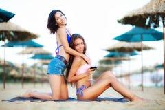Sexiga flickor som har vin och gyckel på en strand Royaltyfria Bilder