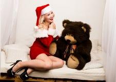 Sexiga julflickaomfamningar med en stor nallebjörn blond kvinna som kläs som jultomten fotografering för bildbyråer