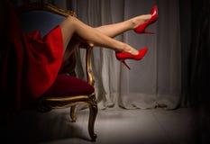 Sexiga kvinnas ben i röda höga häl Arkivbild