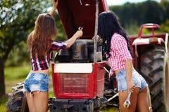Sexiga kvinnliga bönder som fixar traktoren Arkivbild