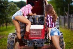 Sexiga kvinnliga bönder som fixar traktoren Fotografering för Bildbyråer