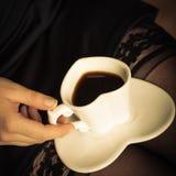 Sexiga kvinnligben med koppen kaffe Fotografering för Bildbyråer