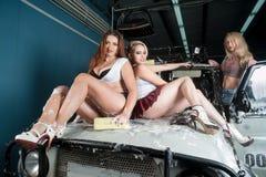 Sexiga kvinnor på biltvagning Arkivbild