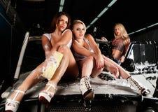 Sexiga kvinnor som tvättar bilen Arkivbild