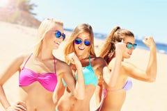 Sexiga kvinnor som visar muskler på stranden Fotografering för Bildbyråer