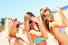 Sexiga kvinnor som visar muskler på stranden Royaltyfri Bild