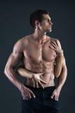 Sexiga muskulösa man- och kvinnlighänder som rymmer hans bröstkorg Fotografering för Bildbyråer