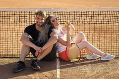Sexiga par Förälskade lyckliga par sitter på tennis netto på domstolen Royaltyfria Foton