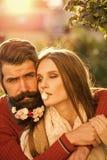 Sexiga par Flicka och man med blommor på skägg Royaltyfria Foton
