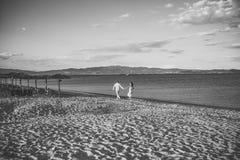 Sexiga par Man- och kvinnahållhänder, kopplar ihop lyckligt på semester Förälskad ställning för par på stranden, kust bröllopsres Arkivfoton