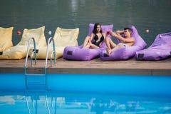 Sexiga par som kopplar av med drinkar på dämpade dagdrivare av simbassängen och floden på bakgrunden Arkivfoto