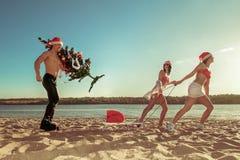 Sexiga Santas som drar jultomten på stranden Royaltyfria Bilder