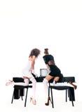 Sexiga två kvinnor på kontoret med en bärbar dator Fotografering för Bildbyråer
