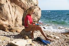 Sexigt dykareflickasammanträde på klippan av den steniga stranden och förberedelsen arkivfoto