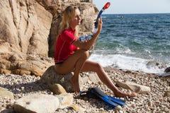 Sexigt dykareflickasammanträde på klippan av den steniga stranden och förberedelsen fotografering för bildbyråer
