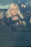 Sexigt flickasammanträde bak hjulet av en bil Royaltyfria Foton