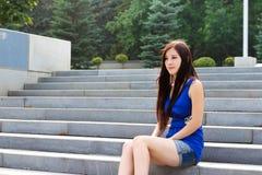 Sexigt flickasammanträde på trappan i parkera Arkivfoton
