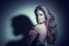 sexigt kvinnabarn för stående Förförisk brunettflicka som poserar i mörker Skönhetglamourdam med långt lockigt hår royaltyfri fotografi