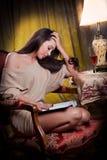 Sexigt kvinnasammanträde i wood stol och läsning i en tappningplats Arkivbild