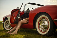 Sexigt lägger benen på ryggen och sportbilen fotografering för bildbyråer
