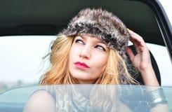 Sexigt modeflickasammanträde i en bil Arkivfoto
