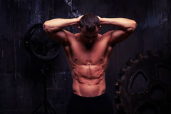Sexigt muskulöst mananseende med händer bak hans huvud, hans abs p Royaltyfri Fotografi