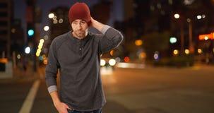Sexigt stads- millennial anseende bredvid gatan på natten Arkivbild