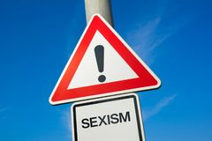 Sexism. Traffic sign with exclamation mark to alert, warn caution - precaution and warning of violent and offensive attack and assault that is based on sex Royalty Free Stock Photography